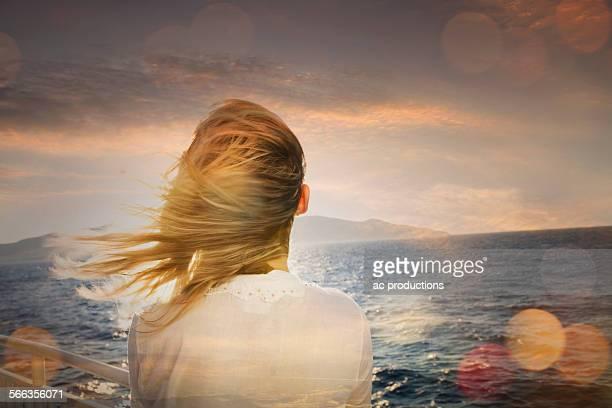 Caucasian woman standing on boat admiring ocean