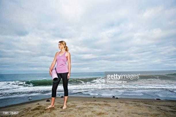 Caucasian woman standing on ocean beach holding exercise mat