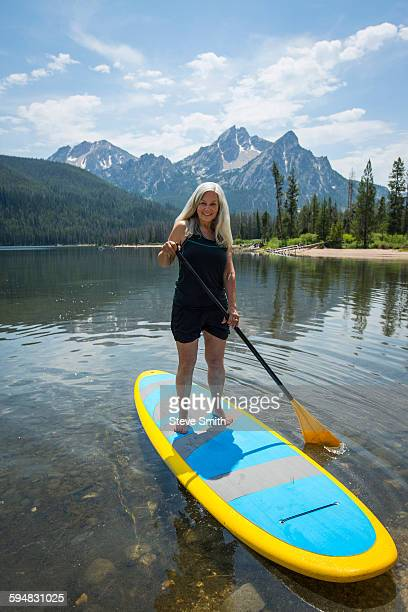 Caucasian woman standing on paddle board in lake