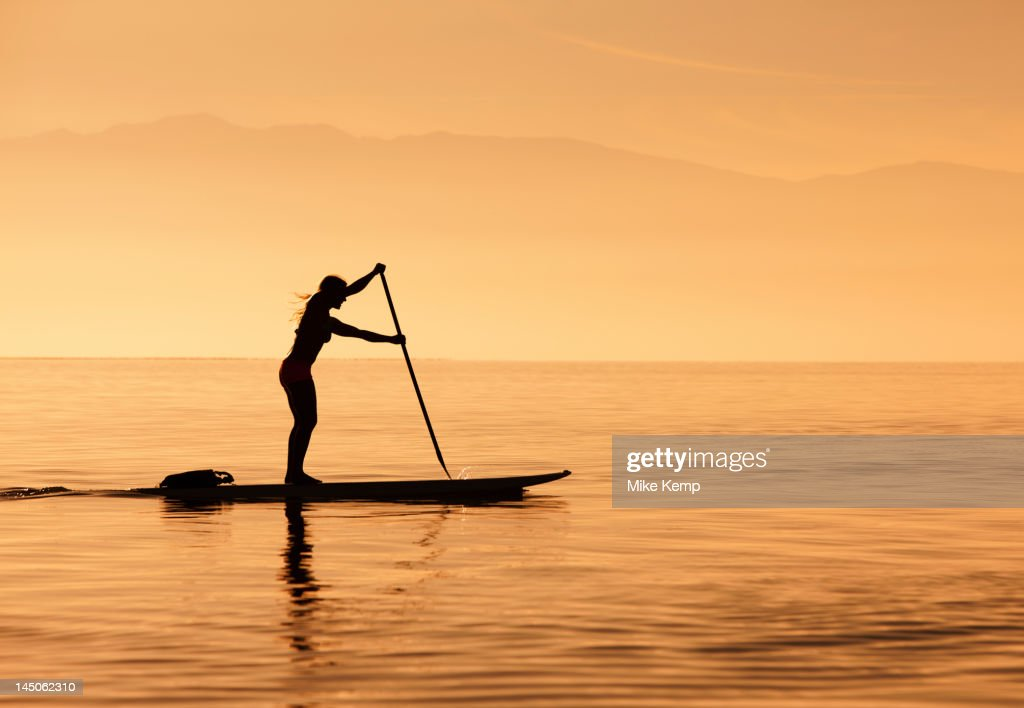 Caucasian woman standing on paddle board