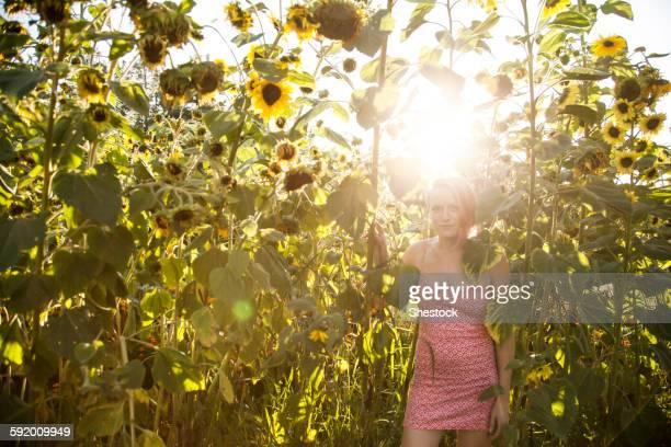 Caucasian woman standing under sunflowers in garden
