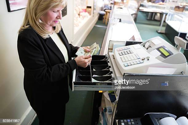 Caucasian woman store owner puts money from sale in register