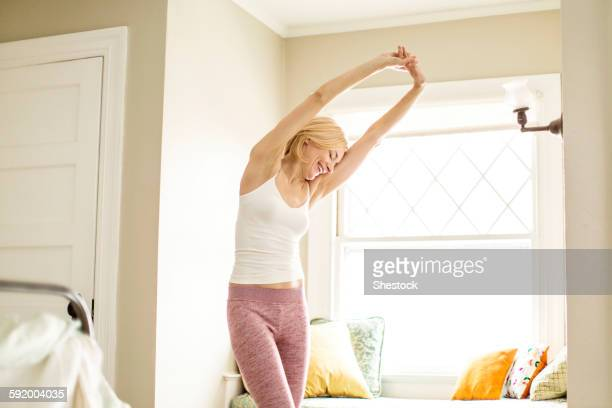 Caucasian woman stretching in bedroom