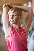 Caucasian woman stretching in gym