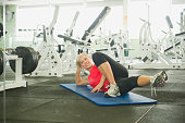 Caucasian woman stretching in gymnasium