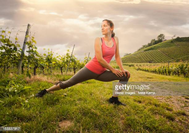 Caucasian woman stretching in vineyard