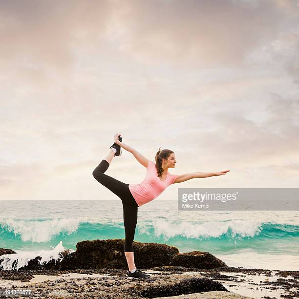 Caucasian woman stretching on beach