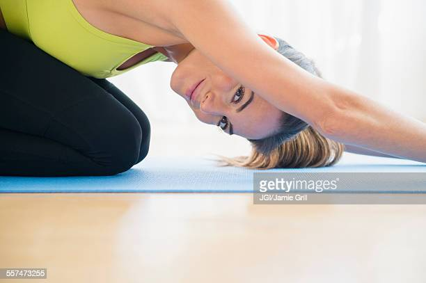 Caucasian woman stretching on yoga mat
