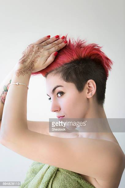 Caucasian woman styling dyed hair