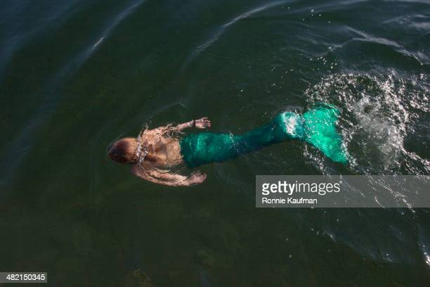 Caucasian woman swimming in mermaid costume in still lake