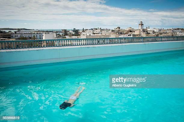 Caucasian woman swimming in urban rooftop pool