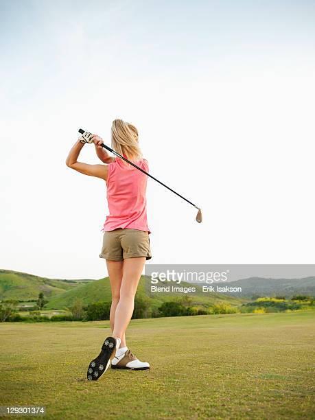 Caucasian woman swinging golf club on golf course