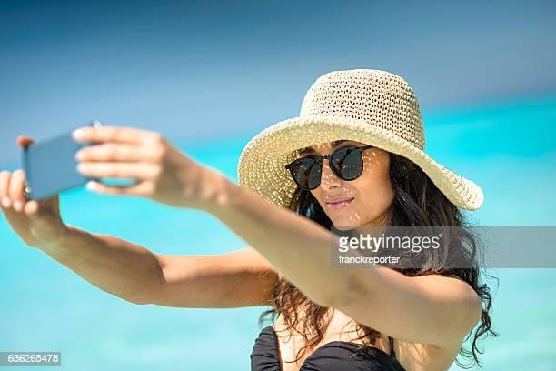 Mujer caucásica tome un autorretrato en la playa del caribe