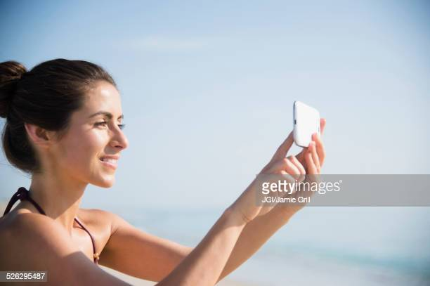 Caucasian woman taking selfie with cell phone at beach