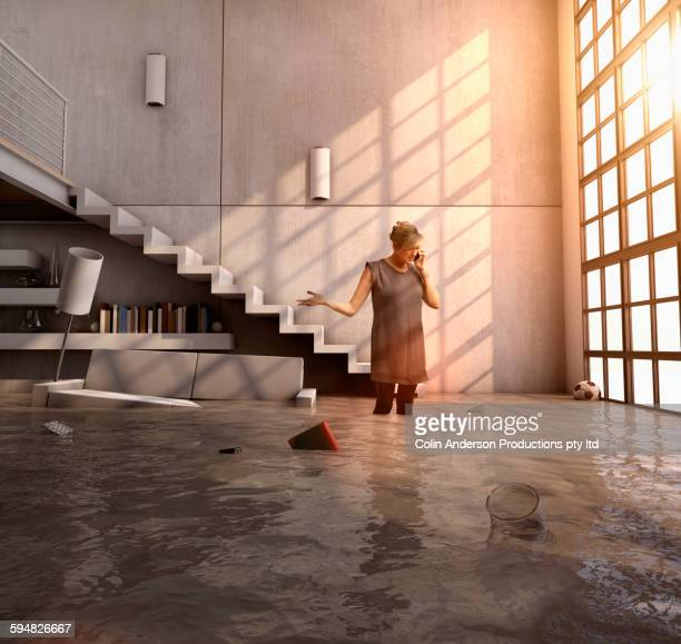 Caucasian woman talking on cell phone in flooded house