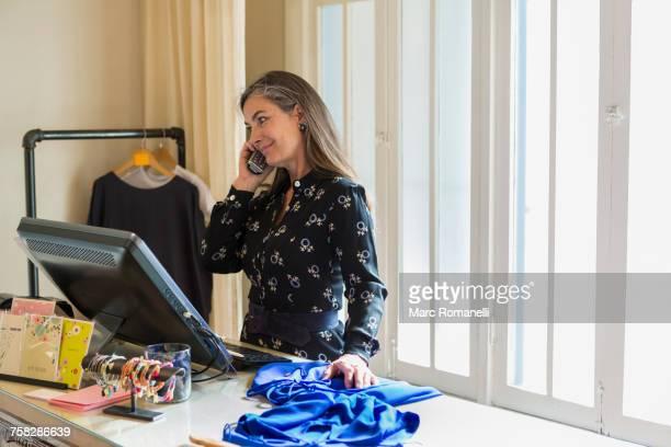Caucasian woman talking on telephone near computer