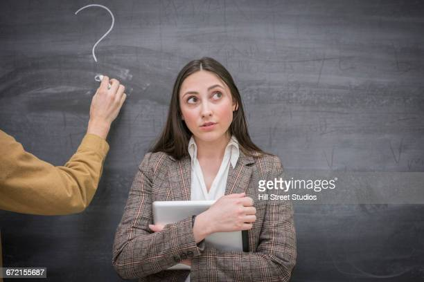 Caucasian woman thinking next to question mark on blackboard in classroom