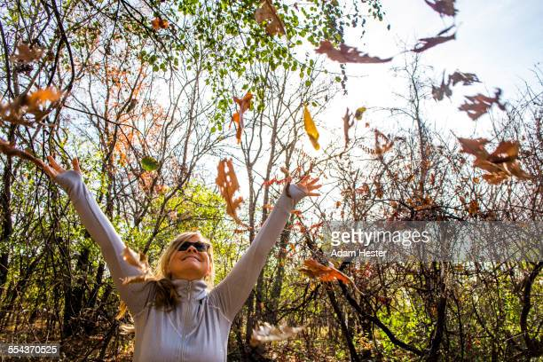 Caucasian woman throwing autumn leaves in forest