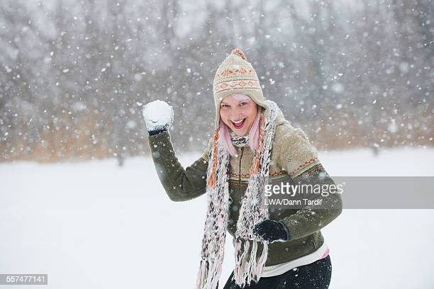Caucasian woman throwing snowball in field