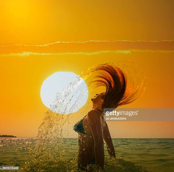 Caucasian woman tossing hair in ocean under sunset sky