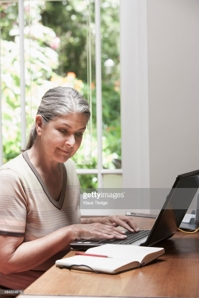 Caucasian woman transcribing journal : Stock Photo
