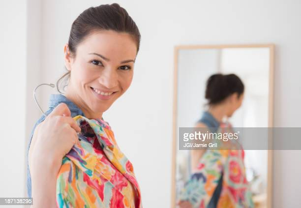 Caucasian woman trying on clothes in store