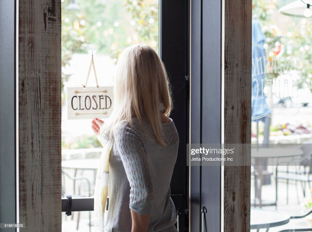 Caucasian woman turning sign in shop window