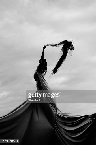 Caucasian woman twirling in fabric under clouds