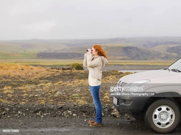 Caucasian woman using binoculars on remote road