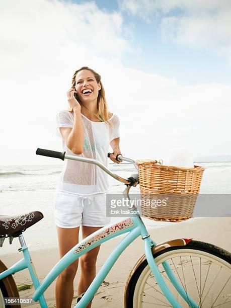 Caucasian woman using cell phone on beach