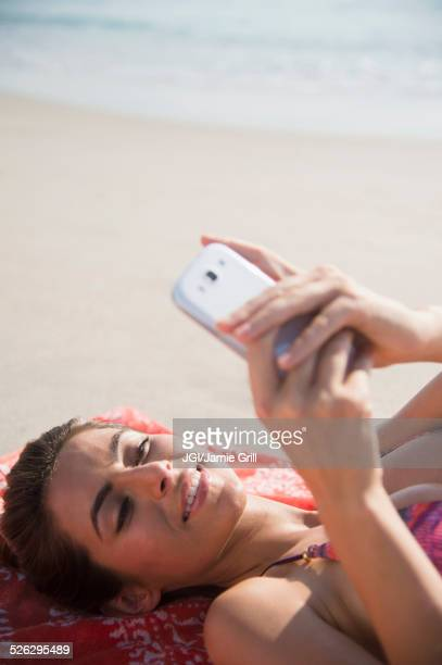 Caucasian woman using cell phone on beach