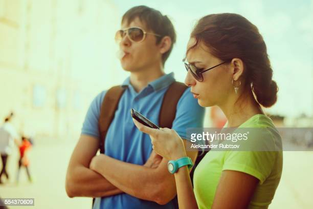 Caucasian woman using cell phone with boyfriend outdoors
