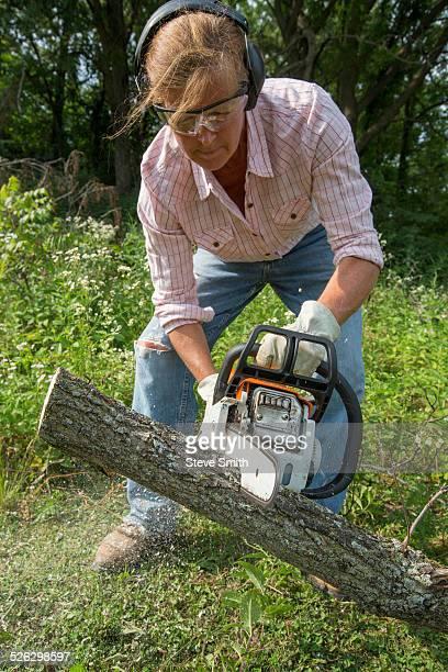 Caucasian woman using chain saw to cut wood
