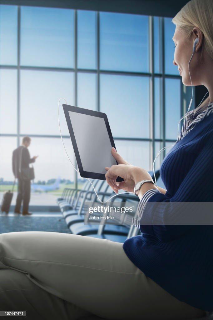 Caucasian woman using digital tablet in airport : Stock Photo