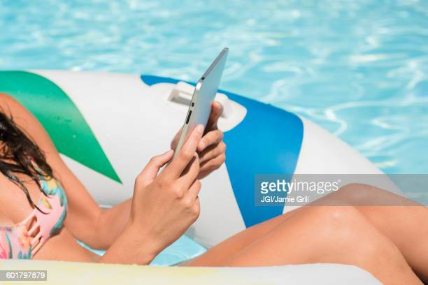 Caucasian woman using digital tablet in swimming pool