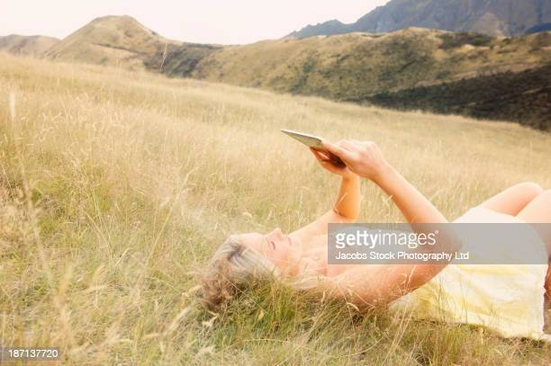 Caucasian woman using digital tablet in tall grass