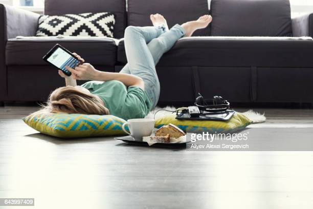 Caucasian woman using digital tablet on floor