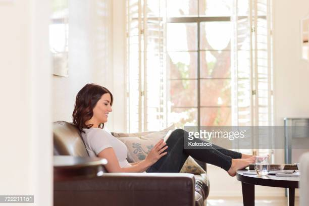 Caucasian woman using digital tablet on sofa