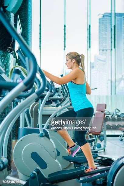 Caucasian woman using elliptical machine in gym