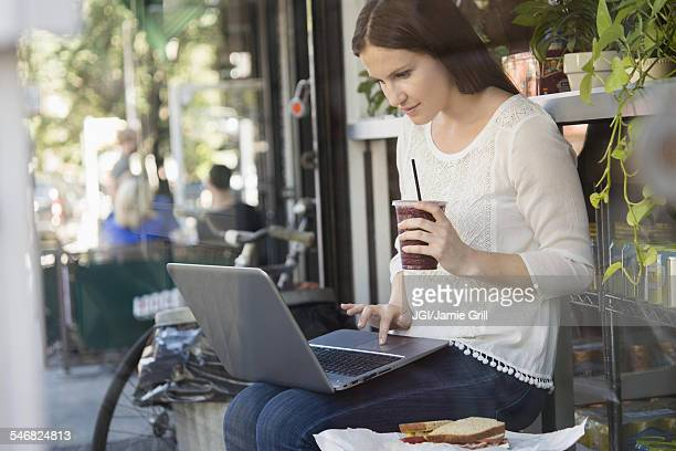 Caucasian woman using laptop and drinking coffee outside cafe