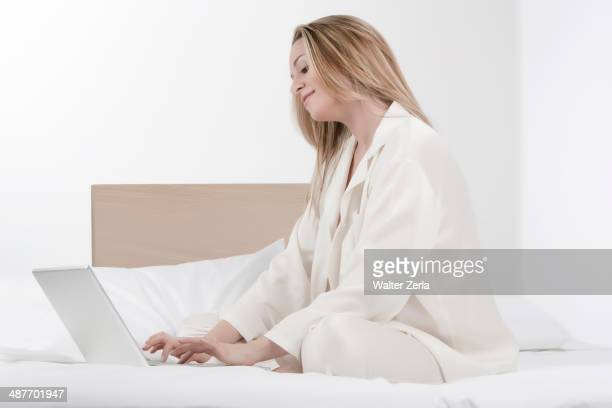 Caucasian woman using laptop on bed