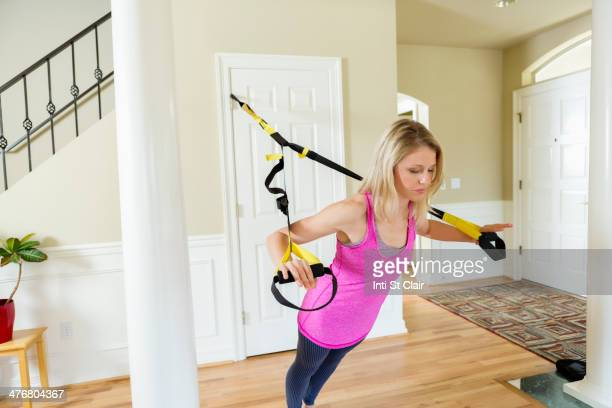 Caucasian woman using resistance band equipment in home