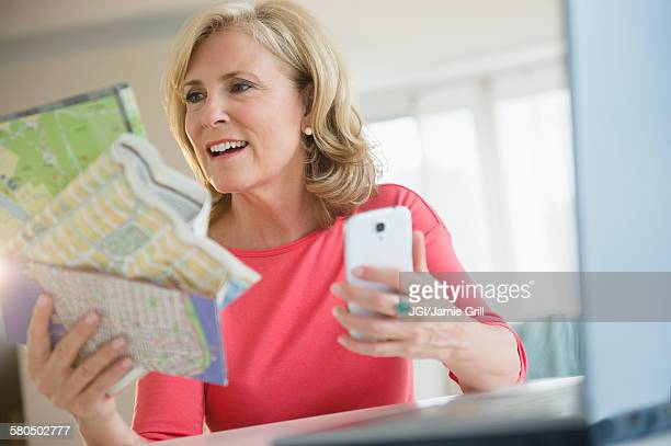 Caucasian woman using roadmap and cell phone to plan trip