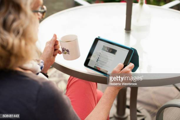 Caucasian woman using tablet computer outdoors