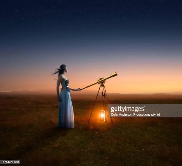 Caucasian woman using telescope