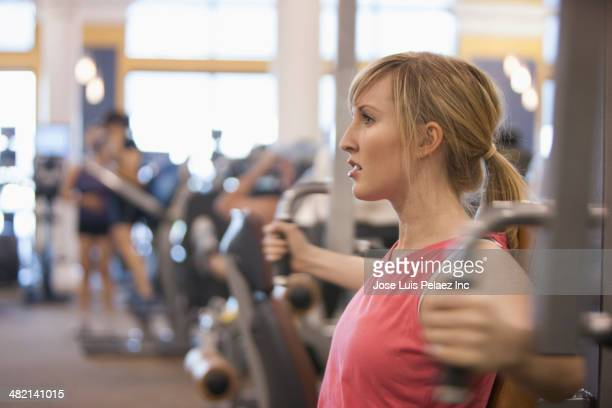 Caucasian woman using weight machine in gym