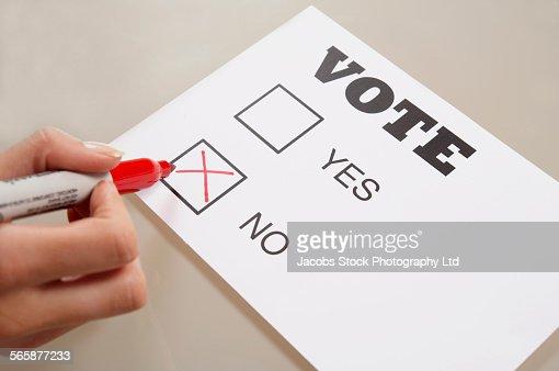 Caucasian woman voting no on ballot