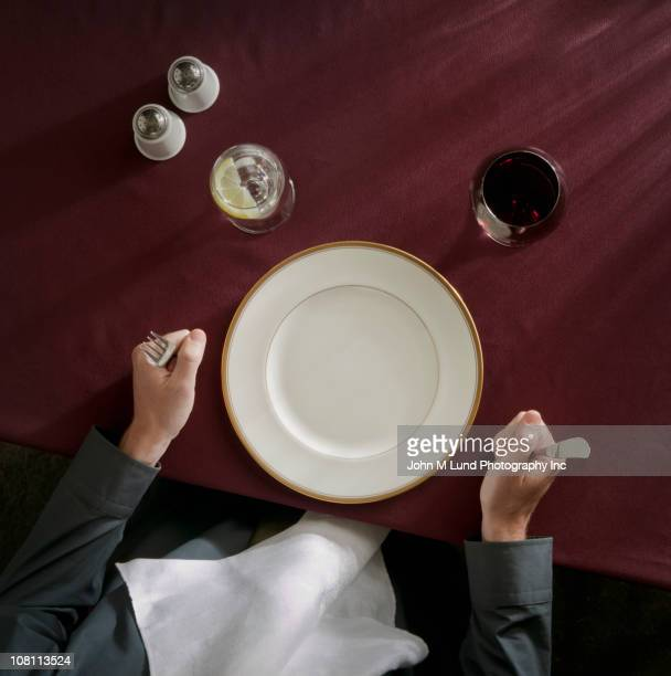 Caucasian woman waiting in front of empty plate