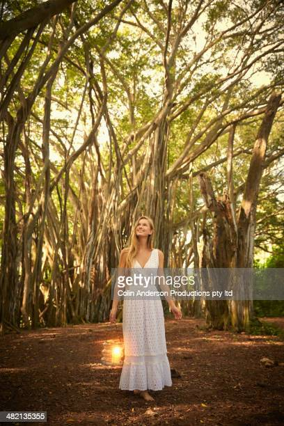 Caucasian woman walking below banyan trees in forest
