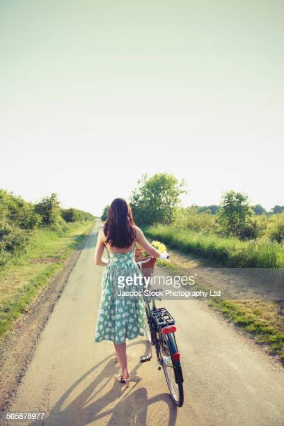 Caucasian woman walking bicycle with basket of flowers